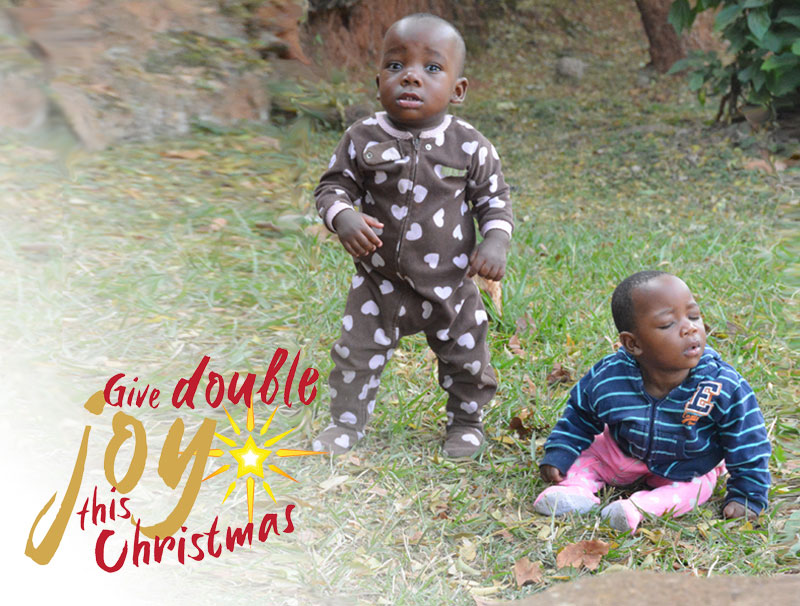 Two small toddlers are pictured on some grass. One, Wasswa, is standing with eyes open, wearing a brown jumpsuit. The other, Jamira, is sitting with her eyes closed, wearing a striped top and pink leggings. She is hunched over and does not look like she is supporting herself well.